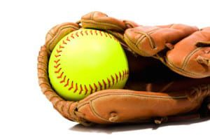 A new flourescent yellow Softball in a glove against a white background