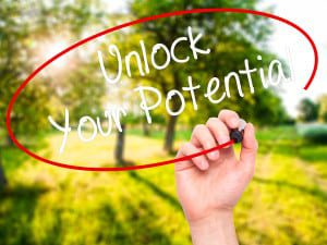 Man Hand writing Unlock Your Potential with black marker on visual screen. Isolated on nature. Business technology internet concept. Stock Photo